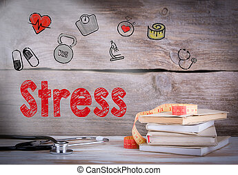 Stress Concept. Stack of books and a stethoscope on a wooden background