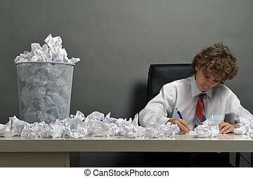 Stress concept - Young businessman next to stack of crumpled...