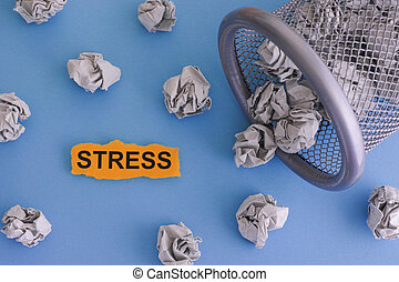 Stress. Grey crumpled paper balls rolling out of a trash can