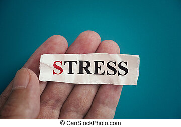 Man holding a piece of paper with the word Stress on it