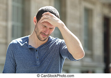 Stressed adult man suffering headache in the street