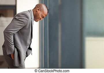 stressed african american businessman bang hi head against...