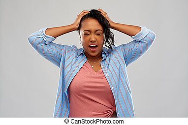 stressed african american woman holding to head