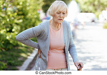 Stressed aged woman feeling bad in the park