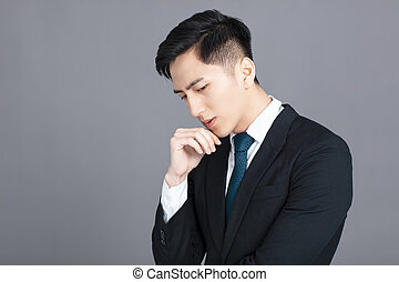 Stressed and confused young business man on gray background