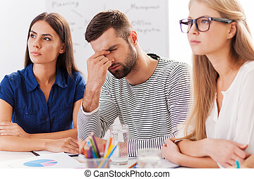 Stressed and tired. Depressed young man touching face with hand while sitting at the table together with his colleagues