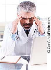 Stressed and tired doctor. Depressed mature grey hair doctor touching his head with hands while sitting at his working place