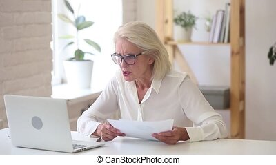 Stressed angry old businesswoman annoyed about computer problem throwing paper