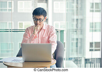 Stressed Asian businessman using laptop in living room