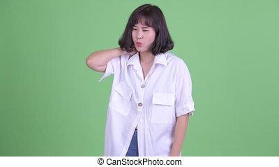 Stressed Asian businesswoman having neck pain