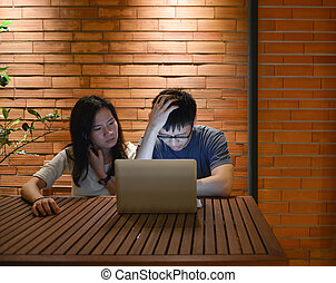 Stressed Asian couple are working together at night, having problems