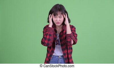 Stressed Asian hipster woman having headache