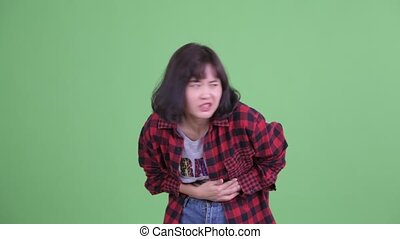Stressed Asian hipster woman having stomachache