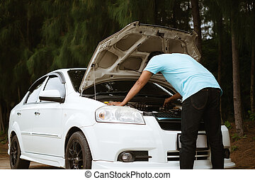 Stressed asian man looking at the engine of broken car