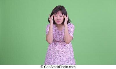 Stressed Asian pregnant woman having headache