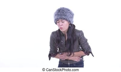 Studio shot of beautiful Asian woman wearing fur hat ready for winter isolated against white background