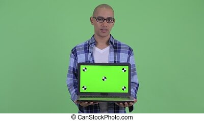 Stressed bald hipster man showing laptop - Studio shot of...