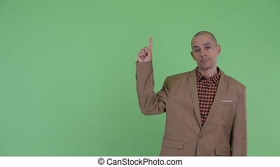 Stressed bald multi ethnic businessman pointing up - Studio...