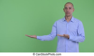 Stressed bald multi ethnic businessman showing something -...