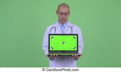Stressed bald multi ethnic man doctor showing laptop -...