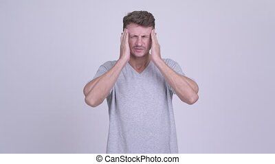 Stressed bearded man having headache - Studio shot of...