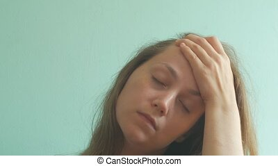 Stressed brown hair woman with headache on pastel mint background. Tired young lady without make-up feel pain, massaging temples. Hard to wake up, morning concept. PMS premenstrual syndrome problems.