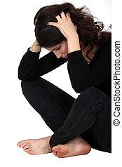Stressed brunette sitting on the floor