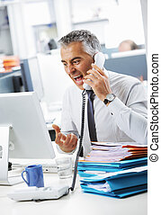 Stressed business man shouting at phone in office