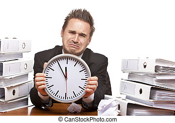 Young businessman is sitting on desk and crying because of unmanageable work and time pressure. Isolated on white.