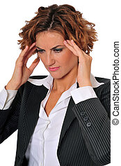 A beautiful stressed business woman with a headache, massaging her temples.