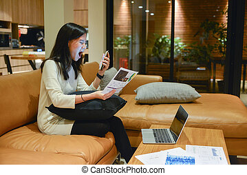 Stressed business woman talking on the phone in living room at night