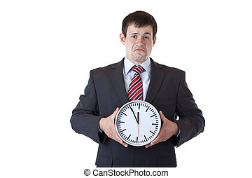 Stressed businessman holds clock in front and looks depressed