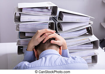 Stressed Businessman In Front Of Stacked Folders