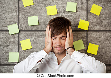 Stressed Businessman - Stressed businessman holding his head...
