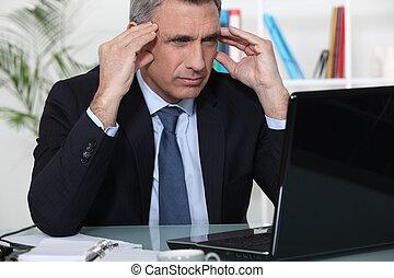 Stressed businessman sat at desk