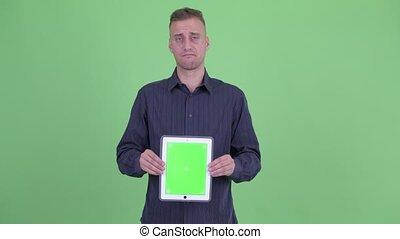 Stressed businessman showing digital tablet