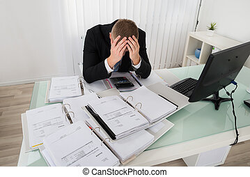 Stressed Businessman Sitting At Office Desk