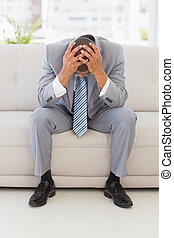 Stressed businessman sitting on couch