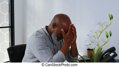Stressed businessman sitting on desk with hand on forehead...
