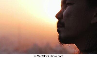 Stressed businessman smoking a ciguarette against city landscape in slow motion