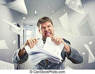 Stressed businessman tearing out stack