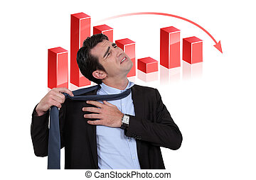 Stressed businessman with a downturn graph