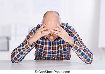 Stressed Businessman With Head In Hands At Desk