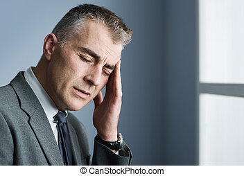 Stressed businessman with headache - Mature businessman with...