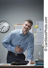 Stressed businessman with stomachache leaning to his desk.