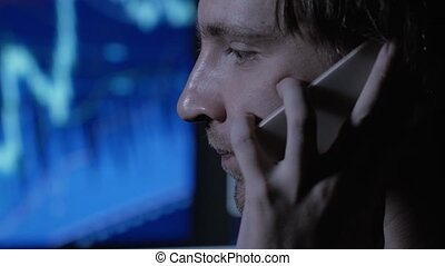 Stressed businessman working overtime late at night in the living room with telephone, computer.