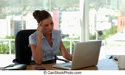 Stressed businesswoman typing on her laptop