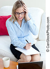 Stressed businesswoman taking notes