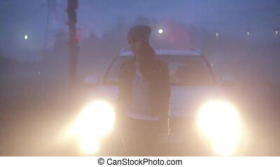 Stressed Caucasian girl standing near headlights. Worried...