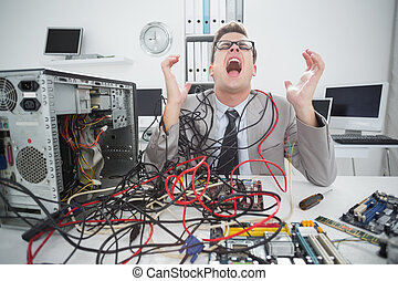 Stressed computer engineer working on broken cables in his ...